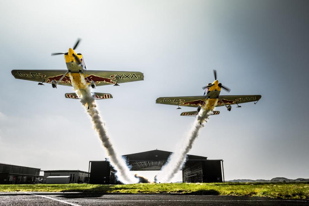 Dos aviones un hangar y una acrobacia aérea